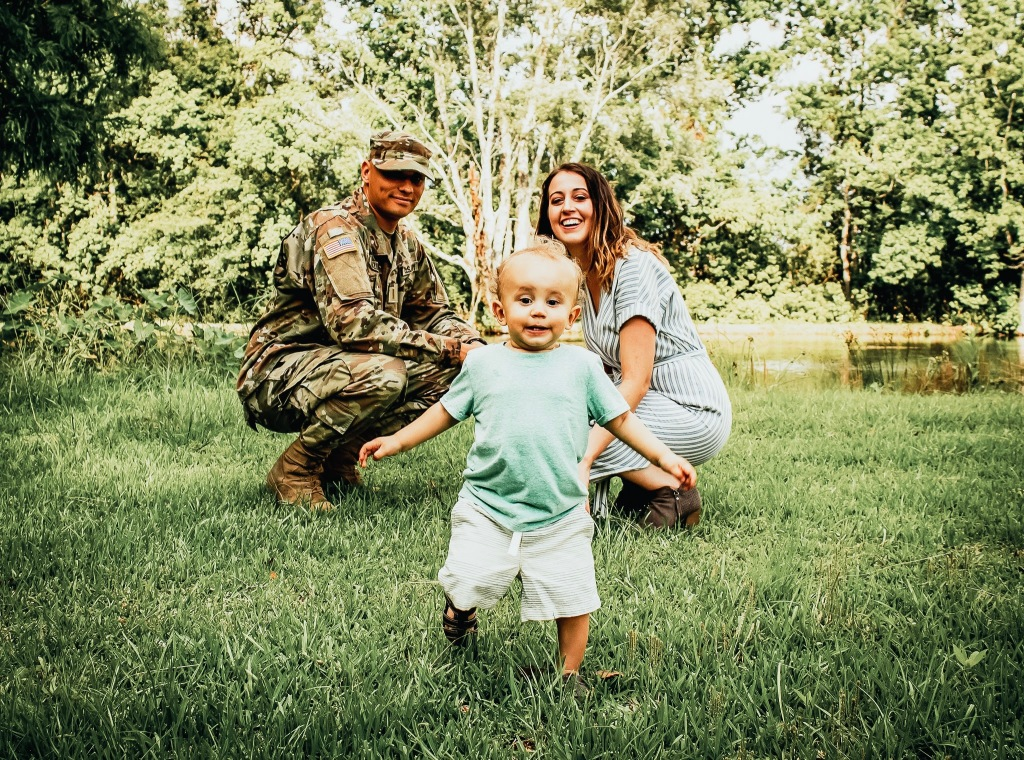 Military Kid Running Towards the Camera while His Mom and Dad Watch by Sarah Mozingo