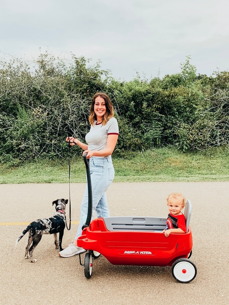Sarah Mozingo walking Lola and pulling Izzy in a wagon