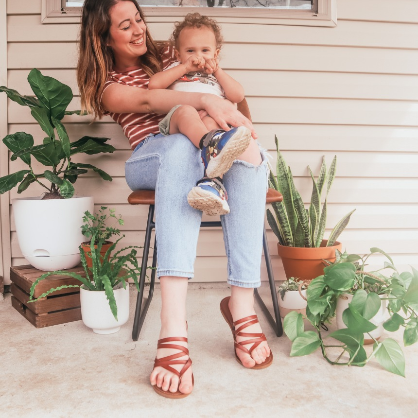 Sarah Mozingo and son sitting in chair surrounded by plants