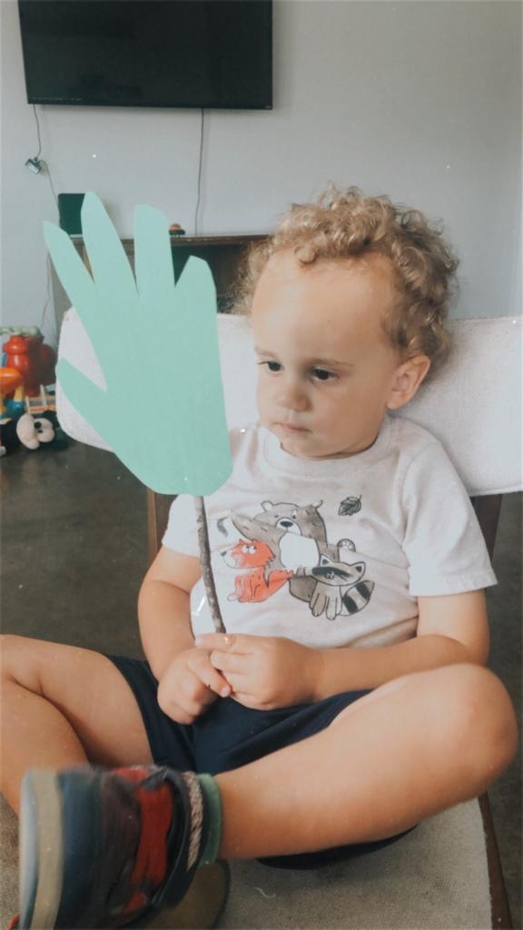 Child holding palm branch craft